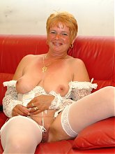 red mature slut playing with herslef on her couch